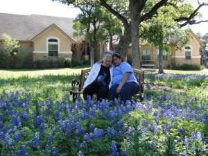 Quality assurance manager Hortencia Torres and resident Winnie take a picture in the Central Texas bluebonnets in front of Tiffin House